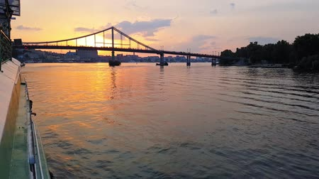 hajózik : 4K. The ship sails on the wide river Dnieper with large bridges before sunset