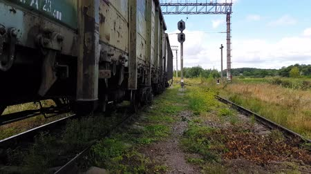 goederentrein : 4K walking along a rut overgrown with grass at the old train station near the freight train chassis