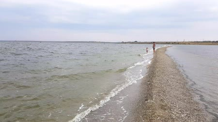 plivat : Beautiful view of family walking along spit. Mom and little daughter walk on the spit in early autumn