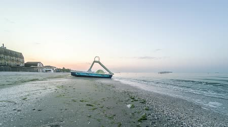 catamaran : 4K timelapse of sunrise over the beach near the sea. Sunrise meadow timelapse over the sea. Catamaran stands near the sea during sunrise. Stock Footage