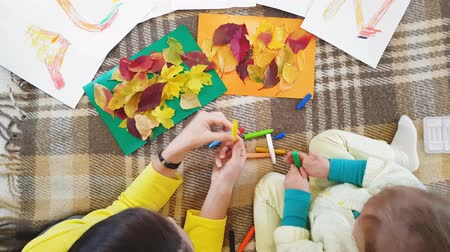 ткачество : Young mother and daughter draw oil pastels inscription Autumn on white sheets of paper and make an applique. Little girl with mom draw oil lettering Autumn inscription on white sheets of paper. Стоковые видеозаписи