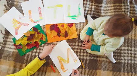güzel sanatlar : Young mother and daughter draw oil pastels inscription Autumn on white sheets of paper and make an applique. Little girl with mom draw oil lettering Autumn inscription on white sheets of paper. Stok Video