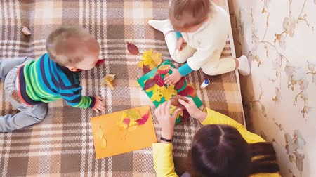 рукоделие : Mom and little daughter make autumn applique from autumn leaves. Little girl with mom glues autumn casting on a cardboard sheet. Making autumn applique at home. Стоковые видеозаписи