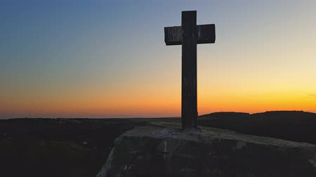 holy heaven : Stone cross on top of a mountain against a sunset. Cross on a sunset background. Stone crem on the mountain at sunset Stock Footage