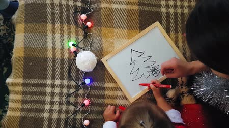 do it yourself : Mom with daughter on the board draw Christmas attributes. Mom and daughter are drawing a Christmas tree. Christmas theme: mom and daughter paint Christmas in a homely festive setting.