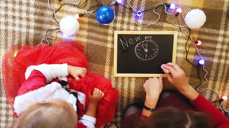 faca : Mom and daughter draw New Year attributes on the blackboard. Mom and daughter are drawing a Christmas tree. New Year theme: mom and daughter paint the new year in a home festive atmosphere.