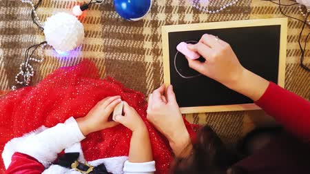 do it yourself : Mom and daughter draw New Year attributes on the blackboard. Mom and daughter are drawing a Christmas tree. New Year theme: mom and daughter paint the new year in a home festive atmosphere.