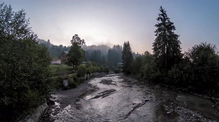 iluminado para trás : 4K timelapse of sunrise over a mountain river in the Carpathians Stock Footage