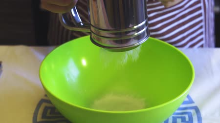 sifting : Close-up slow motion of a female hand sifting flour with a sieve mug in a green bowl in the home kitchen. Cooking pancakes