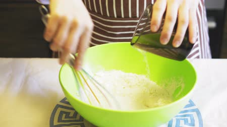 sifting : Close-up of a female hand adds water to flour in a green bowl in the home kitchen. Cooking pancakes Stock Footage