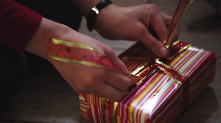 kerstpakket : Close-up of woman and girl hands packing gifts in boxes in Christmas and New Year colors. Stockvideo