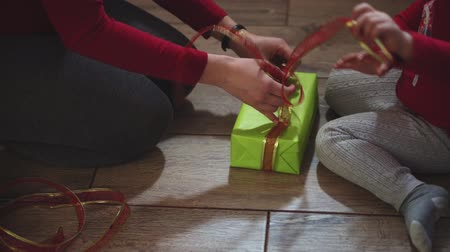 inpakpapier : Close-up of woman and girl hands packing gifts in boxes in Christmas and New Year colors. Stockvideo