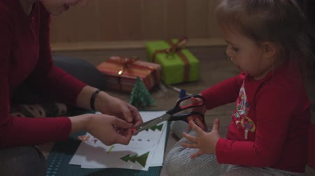 kerstpakket : An average plan mom and little daughter make a snowman with a paper applique. Stockvideo