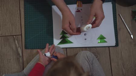 kerstpakket : Close up of woman and little girl hands making snowman with paper applique. Stockvideo