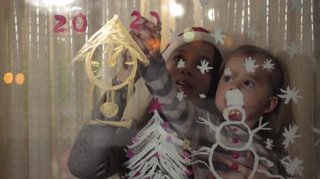budapeszt : Mom and daughter draw a snowman, a Christmas tree and a clock with paints on a window pane. Drawing with acrylics on glass. Wideo