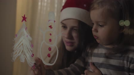 budapeszt : Mom and daughter draw a snowman and a Christmas tree with paints on a window pane. Drawing with acrylics on glass. Wideo