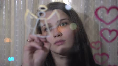 guache : Beautiful girl paints heart and angel on glass Stock Footage