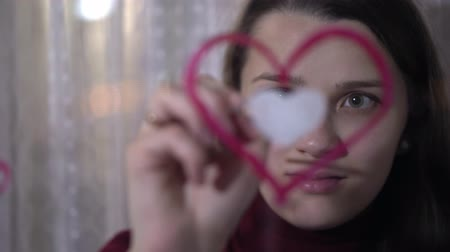 guache : Beautiful girl paints a heart on glass Stock Footage