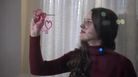 okno : Beautiful girl paints a heart on glass Wideo