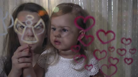 guache : Mom with little daughter draw heart and angel paints on glass.