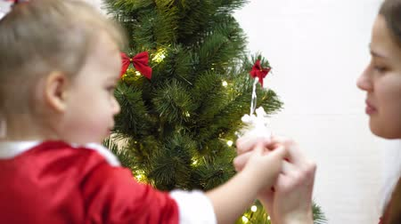 носок : baby and pregnant mom hang red ball toy on Christmas tree. happy childhood concept. child and mother decorate tree with christmas balls. small child and a parent are playing by Christmas tree. Стоковые видеозаписи