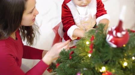 festoon : baby and pregnant mom hang red ball toy on Christmas tree. happy childhood concept. child and mother decorate tree with christmas balls. small child and a parent are playing by Christmas tree. Stock Footage
