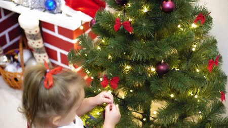 concern : baby and pregnant mom hang red ball toy on Christmas tree. happy childhood concept. child and mother decorate tree with christmas balls. small child and a parent are playing by Christmas tree. Stock Footage