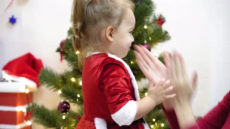 festoon : baby and pregnan mom hang red ball toy on Christmas tree. happy childhood concept. child and mother decorate tree with christmas balls. small child and a parent are playing by Christmas tree.
