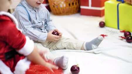 happy socks : baby and pregnant mom hang red ball toy on Christmas tree. happy childhood concept. child and mother decorate tree with christmas balls. small child and a parent are playing by Christmas tree. Stock Footage