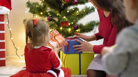 concern : baby and pregnan mom hang red ball toy on Christmas tree. happy childhood concept. child and mother decorate tree with christmas balls. small child and a parent are playing by Christmas tree.