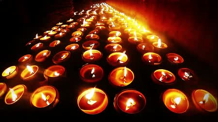 Rows of candle light on ground near the wall