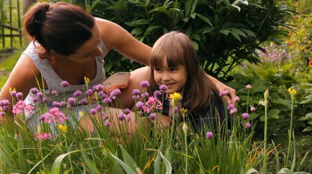 den matek : woman (girl) and the child (daughter) smell flowers in a garden summer day