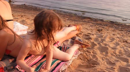 banhos de sol : girl puts a blanket on the beach next to sister