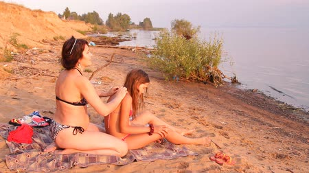 masaż : the mother and a girl on the beach, a woman makes massage