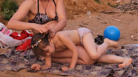 banhos de sol : mother brushed her hair daughter on the beach Vídeos