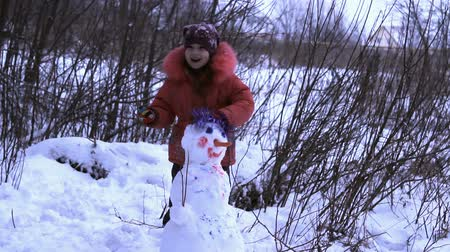 açıklık : the little girl runs around, spinning, jumping, dancing is a snowman, in nature, snow, winter, in the field, around bushes and trees, forest