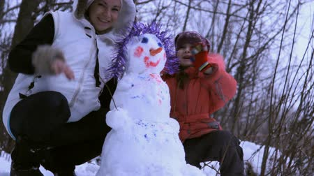 açıklık : woman (mother) and a little girl playing with snowman Stok Video