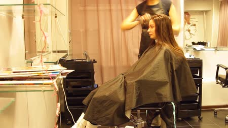 şampuan : the girl sits in the chair in a barbershop, hairdresser works with her hair, color, apply paint, foam, balm, dry, brushing her