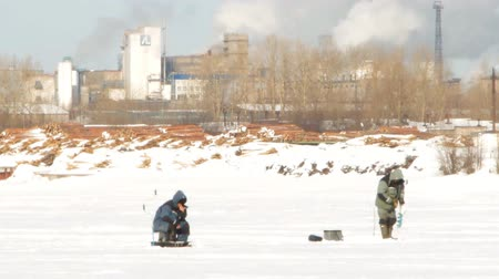 jasně : winter fishing on the background of factory chimneys