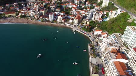 адриатический : Settlement Rafailovici, Budva Riviera, Montenegro. The coast of the city on the Adriatic Sea. Aerial photography. Boats at sea, hotels, villas and apartments on the coast.