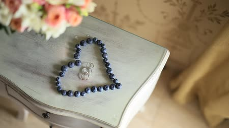 borůvka : Wedding rings in a heart of a blueberry on a table, next to a branch of an olive tree.
