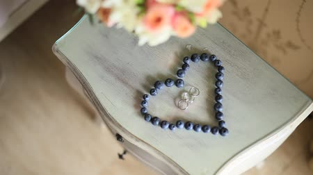 tort weselny : Wedding rings in a heart of a blueberry on a table, next to a branch of an olive tree.