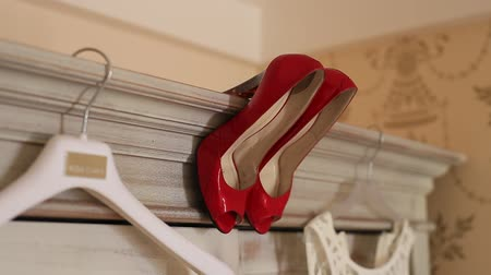 high heel shoe : The brides dress hangs on the hanger on the closet and the red shoes beside her. Wedding in Montenegro. Wedding clothes of the bride.