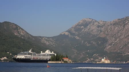 celebrity : Big cruise ship in the Bay of Kotor in Montenegro. Near the island of Our Lady of the Rocks, near Perast. A beautiful country to travel. Stock Footage