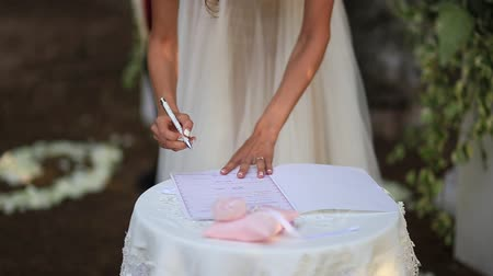 registrar : The bride puts the signature on the wedding.