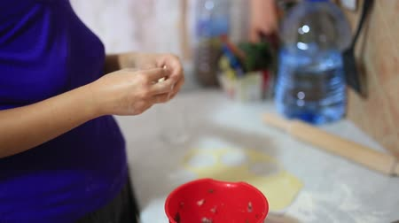 углеводы : She sculpts dumplings in the kitchen. Girl cooking food.