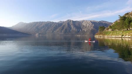 kürek çekme : Kayaks in the lake. Tourists kayaking on the Bay of Kotor, near the town of Perast in Montenegro. Aerial Photo drone. Stok Video