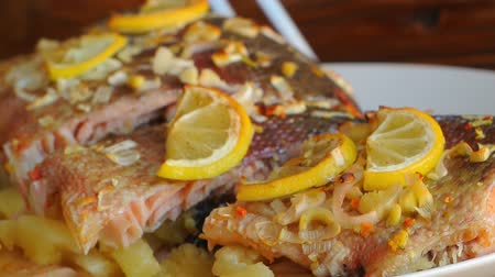 omega : Baked salmon with pineapple and slices of lemon on a plate on a wooden background. Stock Footage