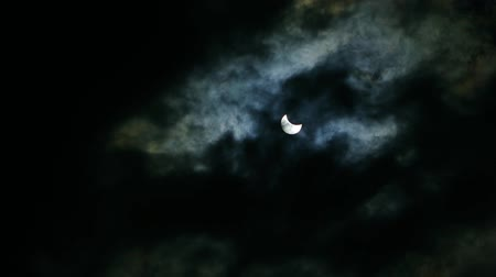 black and white : The eclipse of the sun in the sky. The eclipse through the clouds.