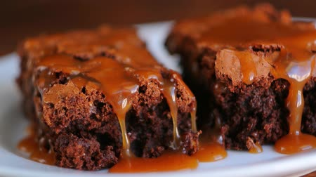 geçiştirmek : Brownie on a plate, on a wooden texture. Watered sweet salty caramel. Several pieces on a plate Stok Video